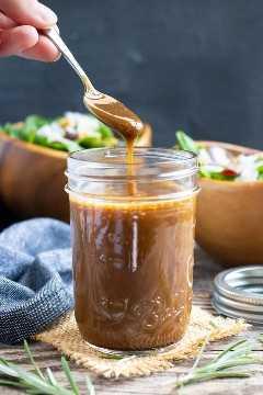 Un frasco de albañil lleno de aderezo para ensaladas balsámico y sirope de arce con dos ensaladas en el fondo.