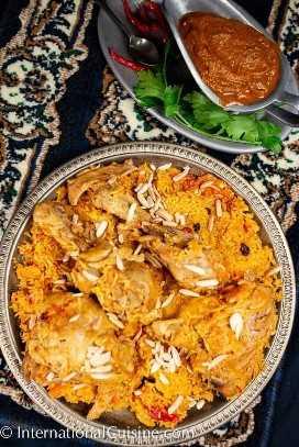 Una fuente llena de arroz y pollo con especias, un plato llamado Al Kabsa, el plato nacional de Arabia Saudita.