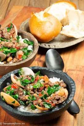 Un encantador tazón de almejas en vino de Oporto cubierto con tomates y espinacas sobre arroz.