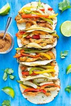 Pollo fajita tacos en una fila con pimientos y cebollas junto al condimento de taco y limas.