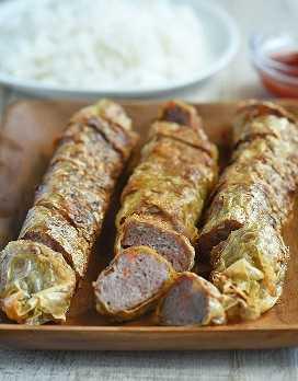 Kikiam de cerdo rebanado rueda en una bandeja de madera con un lado de salsa de tomate para mojar y un plato de arroz al vapor