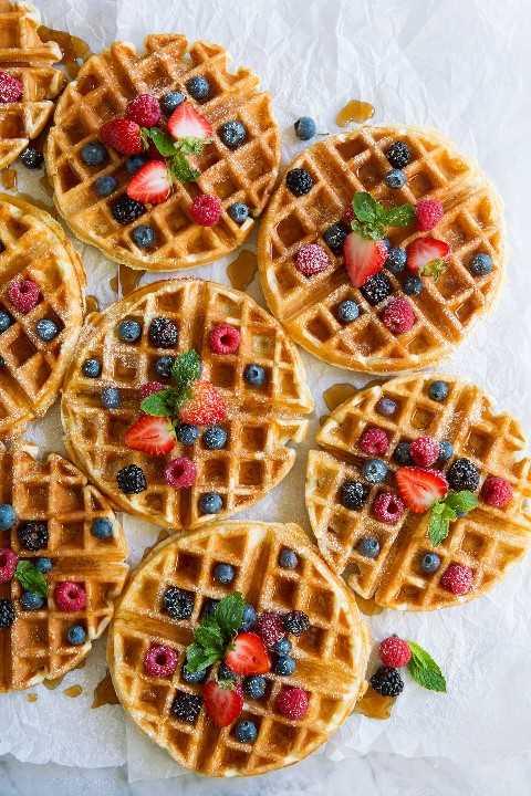 Ocho waffles belgas con bayas y jarabe de arce.