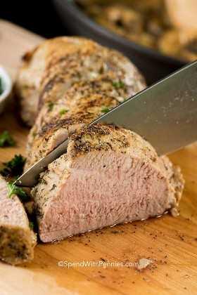 Solomillo de cerdo asado tierno que se corta en una tabla para cortar madera