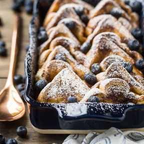 Tostada francesa al horno con azúcar en polvo en una cazuela azul con una cuchara de servir de cobre