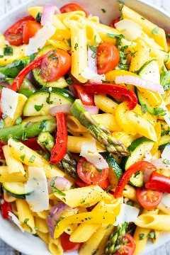 Un gran tazón blanco lleno de una receta de pasta de verduras con tomates, espárragos y pimientos.
