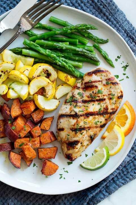 Pollo marinado en un plato de servir con un lado de espárragos, calabaza amarilla, batatas y rodajas de cítricos.