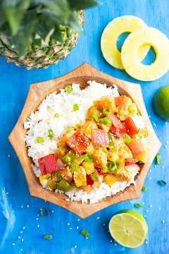Receta fácil de pollo con piña servida con arroz blanco en un cuenco de madera junto a los anillos y las limas de piña.