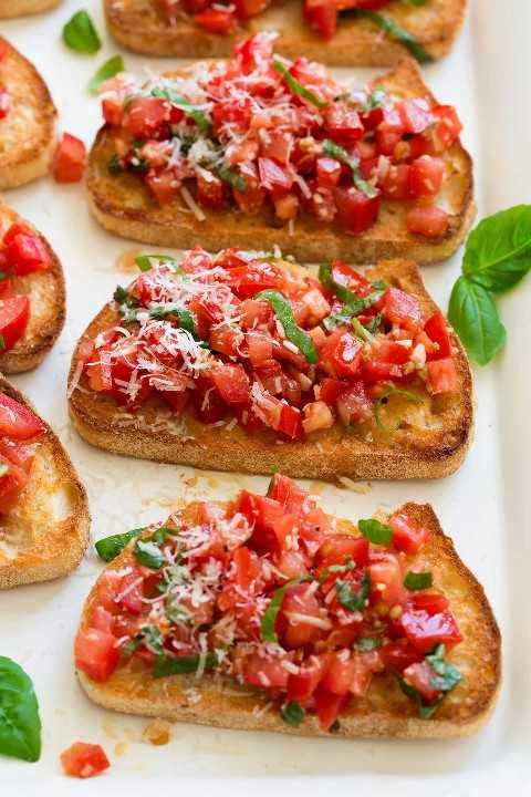 Bruschetta con pan tostado y mezcla de albahaca con tomate fresco encima, sobre una fuente blanca para servir.