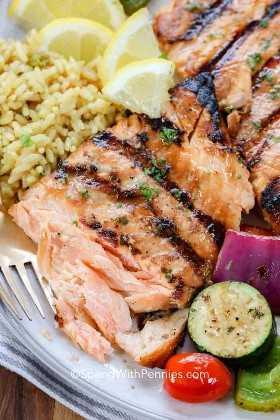 Cerca de un filete de salmón a la parrilla plateado con verduras asadas, arroz y rodajas de limón. Se ha arrancado una pieza que revela cuán flaca y tierna es.