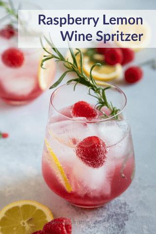 Spritzer de vino de limón y frambuesa servido en un vaso con rodajas de limón, frambuesas y romero para decorar