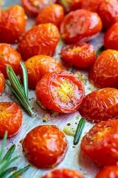 Tomates cherry asados en una bandeja para hornear con romero al lado.