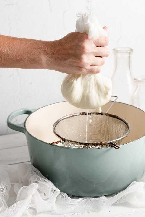 Mano sosteniendo una gasa llena de queso ricotta que está drenando líquido en una olla.