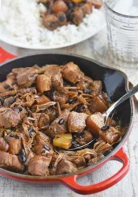 sirviendo humba bisaya con una cuchara grande de una sartén roja