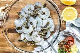 Camarones en un recipiente transparente con ingredientes marinados en un recipiente a un lado.