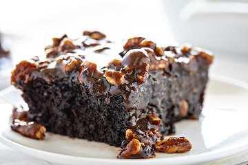 Rebanada de pastel de chocolate negro con glaseado de nuez y mantequilla