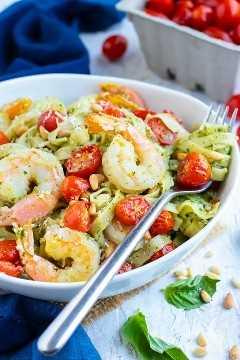 Un cuenco lleno de pasta de camarones al pesto con tomates, queso parmesano y piñones con un cartón de tomates cherry detrás.