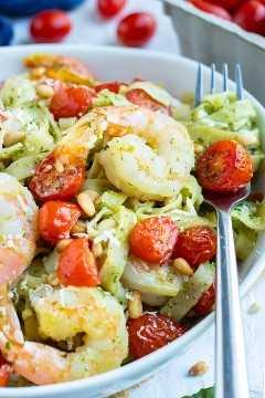 Pasta al pesto saludable con camarones, tomates y piñones.