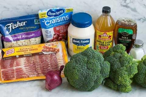 Os ingredientes para fazer a salada de brócolis mostrados aqui incluem brócolis, sal, mel, vinagre de maçã, maionese, cranberries secas, amêndoas fatiadas, bacon e cebola vermelha.