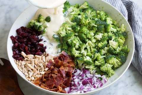 Despeje o molho sobre os ingredientes da salada de brócolis em uma tigela grande e branca.