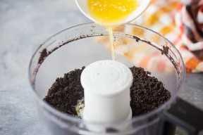Despeje a manteiga derretida nas migalhas de biscoito Oreo para fazer a massa do bolo.