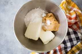 Queso crema, mantequilla de maní, azúcar en polvo y sal en un tazón grande para mezclar.