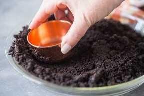 Presionando la masa de galleta Oreo en un molde para pastel con una taza medidora de cobre.