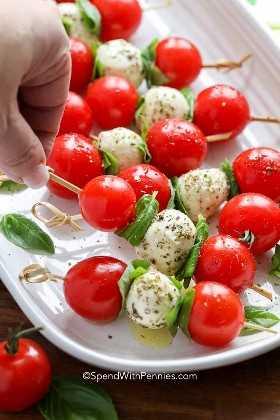 Una brocheta Caprese con tomates cherry, albahaca y mozzarella recogidos de un plato