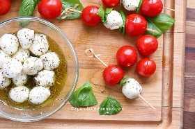 Preparar brochetas caprese con tomates cherry, albahaca y mozzarella marinada en brochetas pequeñas