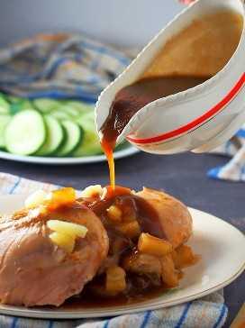 verter salsa de piña en tiniim na manok cortado en una fuente de servir blanca