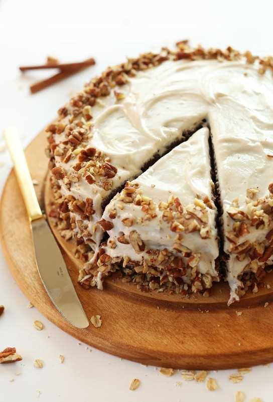 Corte una rebanada de pastel de pan de jengibre de manzana con glaseado de queso crema vegano