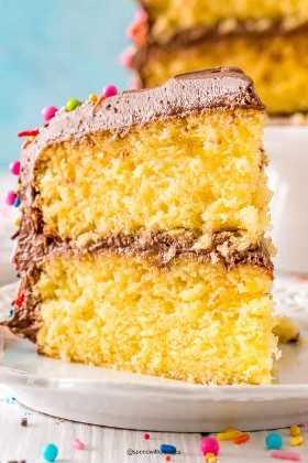 Ciérrese encima de la foto de una rebanada de torta amarilla con el glaseado del chocolate en una placa blanca.