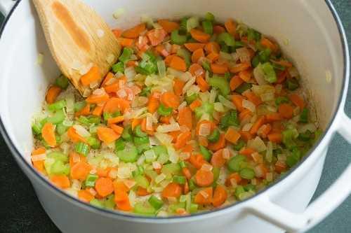 Mostrando cómo hacer sopa de coliflor. Saltear zanahorias, apio, cebolla y ajo en una olla.