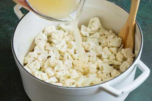 Agregar coliflor y caldo de pollo a la sopa de coliflor.