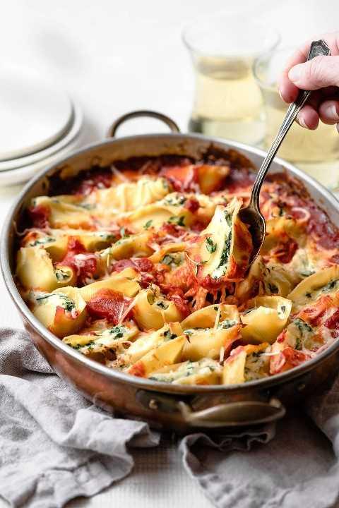 Saca una concha rellena de espinacas y queso de la cacerola.