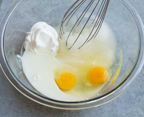Mezcle los huevos, la crema agria, el suero de leche, el azúcar y el aceite en un tazón para panecillos de arándanos.