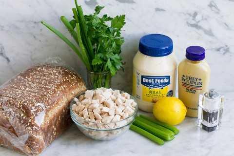 Ingredientes para ensalada de pollo sobre una superficie de mármol que incluyen trozos de pechuga de pollo cocida, apio, limón, mayonesa, mostaza dijon, perejil, cebolla verde, sal y pimienta y pan para servir.