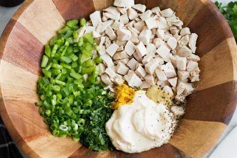 Mostrando cómo hacer ensalada de pollo, tirando trozos de pechuga de pollo, mayonesa, dijon, limón, apio, cebolla verde, perejil en un tazón de madera.