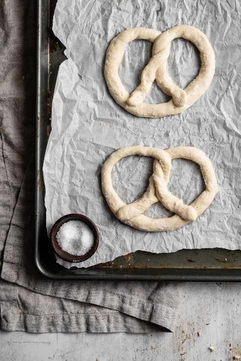 Imagen que muestra cómo hacer pretzels suaves. Da forma a la masa en forma de pretzel y se colocan en una bandeja para hornear forrada con papel pergamino para hornear.