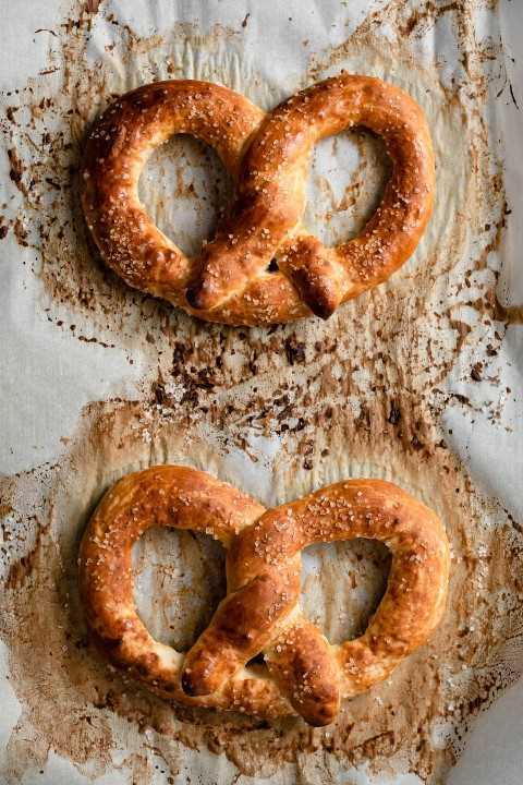 Dos pretzels en una bandeja para hornear forrada con papel pergamino que muestran cómo deberían verse después de hornear con un color marrón dorado.