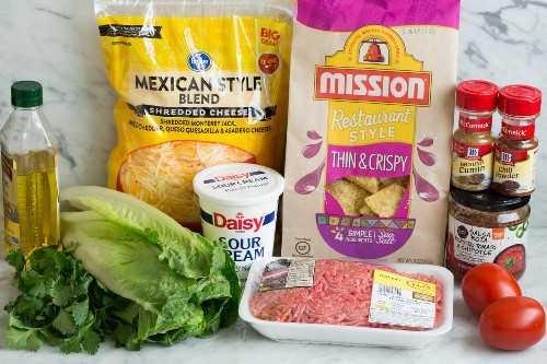 Imagen que muestra los ingredientes necesarios para la ensalada de tacos, incluyendo carne molida, aceite de oliva, especias, salsa embotellada, papas fritas, queso, crema agria, tomates.
