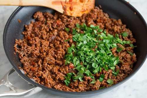 Agregue cilantro a la mezcla de carne de ensalada de taco terminada en una sartén.