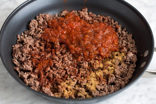 Agregar salsa y especias a la mezcla de carne molida cocida en una sartén grande.