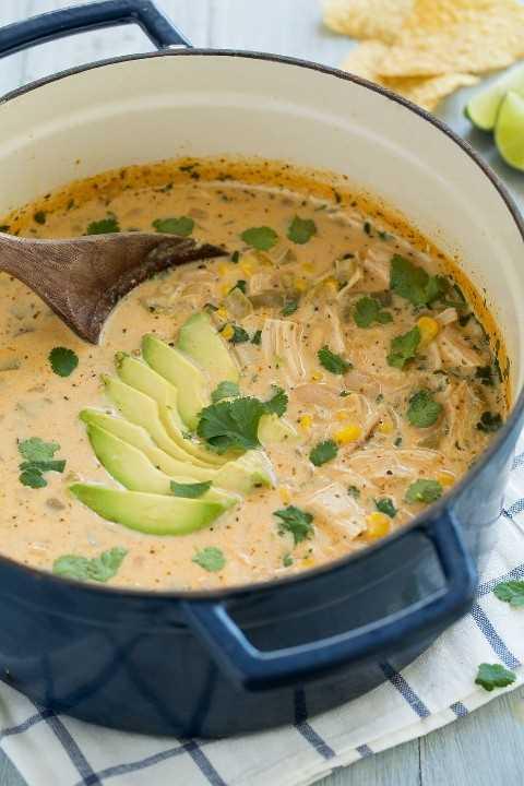 Olla azul marino llena de chile blanco de pollo. El chile incluye trozos de pollo, frijoles pintos, maíz, chiles verdes y un caldo cremoso, se adorna con aguacate y cilantro.