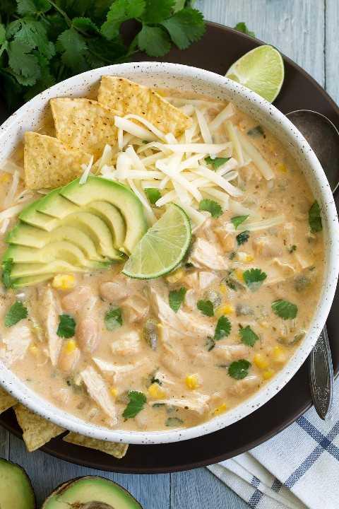 Imagen de arriba de pollo blanco chili en un tazón blanco grande sentado en un plato marrón. El chile se adorna con queso, papas fritas, aguacate, cilantro y lima.