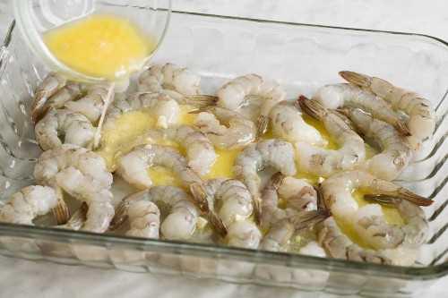 Mostrando cómo hacer camarones al horno. Verter la mantequilla de limón y ajo sobre los camarones en una fuente para horno.