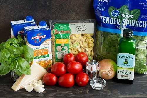Los ingredientes necesarios para hacer la sopa de tortellini que se muestran aquí incluyen tortellini, espinacas, tomates, cebolla, parmesano, ajo, caldo de pollo, albahaca, aceite de oliva.