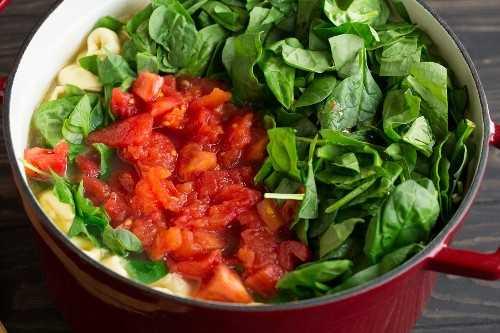 Agregar tomate fresco y espinacas a la sopa de tortellini.