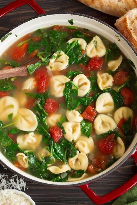 Imagen de arriba de la sopa de tortellini en una olla roja grande.