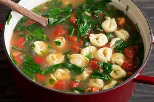 Sopa de tortellini completa en una olla grande de hierro fundido rojo con una cuchara de madera.