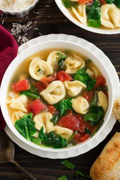 Imagen de arriba de la sopa de tortellini en un tazón blanco.